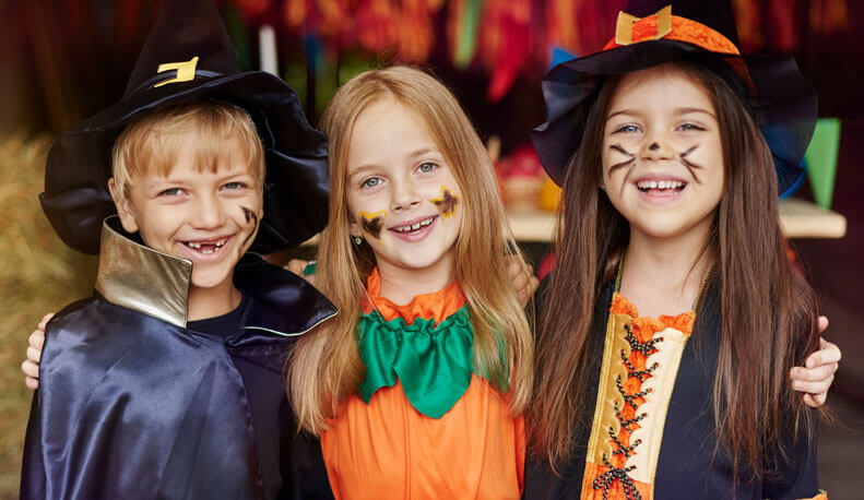 Smiling kids dressed up for Halloween